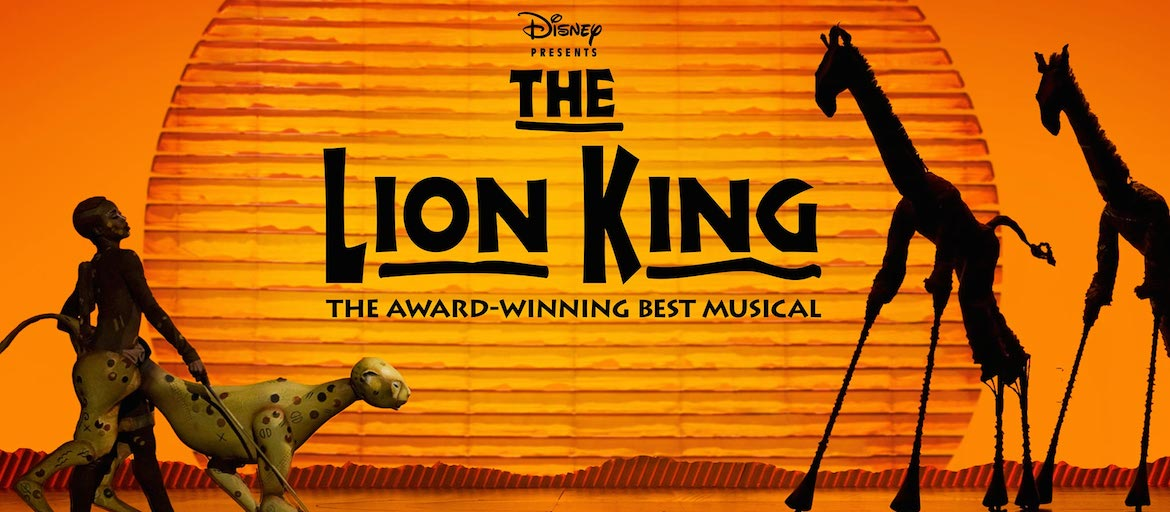 The Lion King logo is written in black in front a sunset. A cheetah and two giraffes look on.
