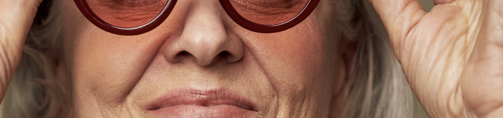 A close up on a face. An older woman's mouth and nose are the focus, her hands and rose-tinted glasses are slightly out of frame.