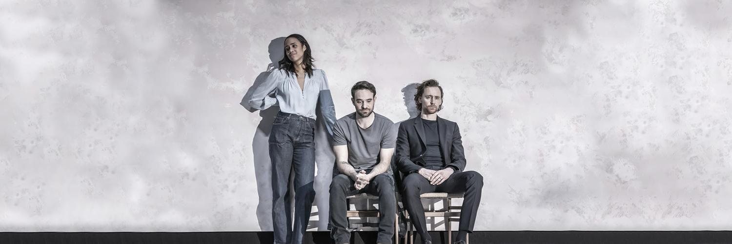 Zawe Ashton stands, while Tom Hiddleston and Charlie Cox sit on wooden chairs. They're in casual clothes with a grey cloud-like background behind them.