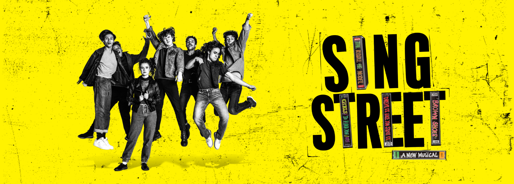 A group of 80s students jump for joy. Sing Street's logo incorporates cassette tape cases into the lettering.